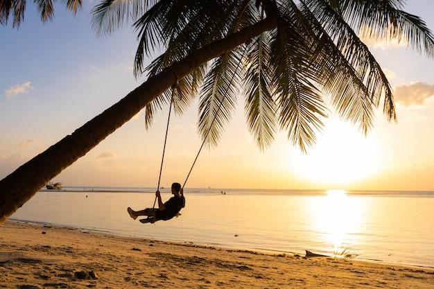 Силуэты парня на качелях висят на пальме, наблюдая закат в воде.