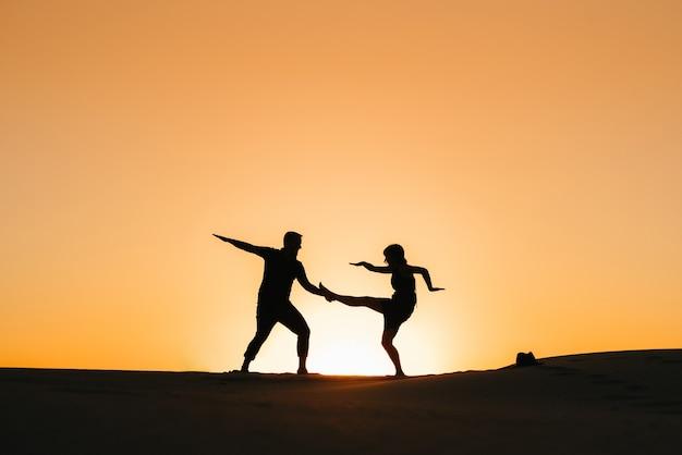 모래 사막에서 오렌지 일몰의 배경에 행복 한 젊은 커플 남자와 여자의 실루엣