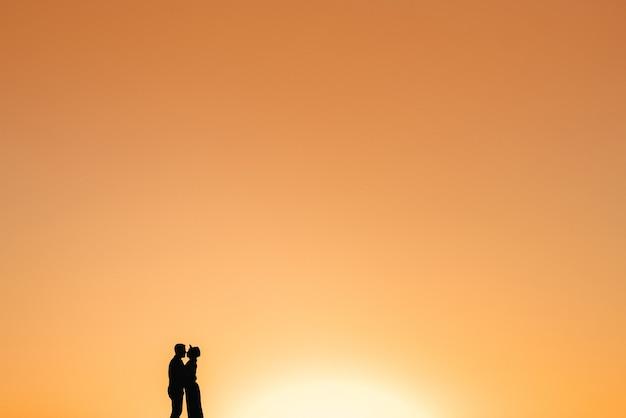 砂の砂漠のオレンジ色の夕日を背景に幸せな若いカップルの男と女のシルエット