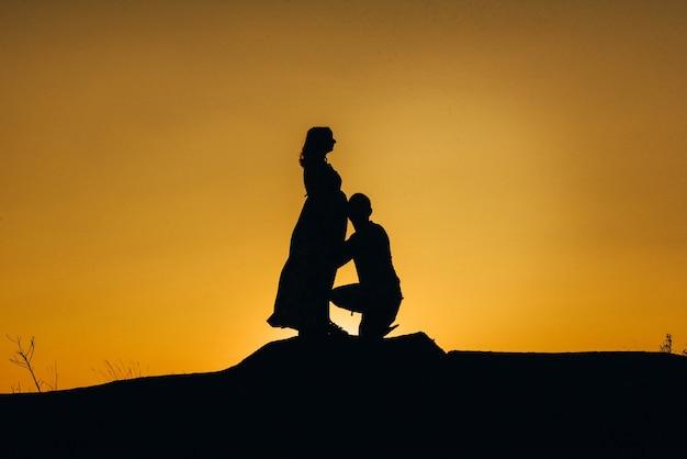Силуэты счастливой молодой счастливой семьи на оранжевом закате в пустыне