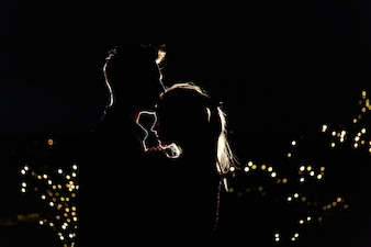 Silhouettes of a lovely young couple standing on the rooftop in the night