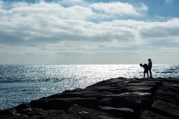 바다에 대 한 돌 부두에 남자와 여자의 실루엣. 스페인 란사로테 섬.