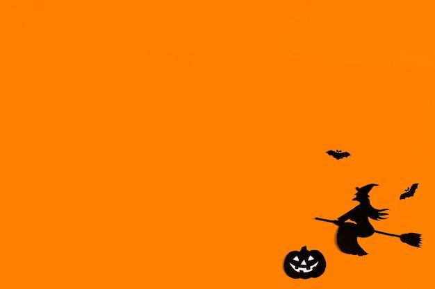 ハロウィーンのオレンジ色の背景に黒い紙コウモリのシルエット