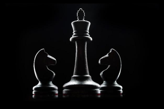 Силуэты шахматных фигур, изолированные на черном фоне. шахматный король и лошади заделывают.
