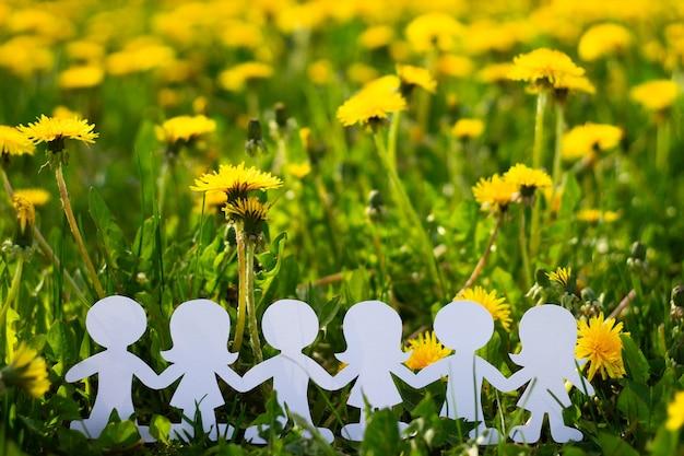 タンポポの背景に段ボールから切り取った手をつないでいる子供のシルエット。白い紙でできた女の子と男の子。国際こどもの日。コピースペース