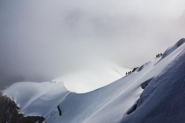 Силуэты альпинистов на вершине снежной горы