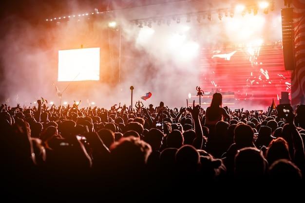 Силуэты концертной толпы. мероприятие с большим количеством людей. ночная вечеринка в большом клубе.