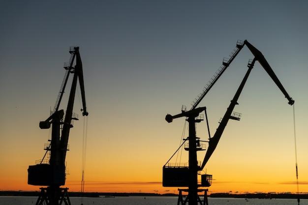 日没時の夕方の港のクレーンのシルエット