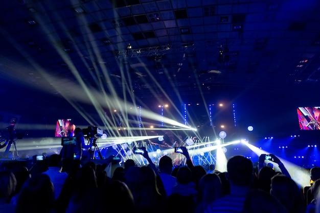 Силуэты толпы зрителей на концерте со смартфонами в руках. сцена красиво освещена прожекторами.