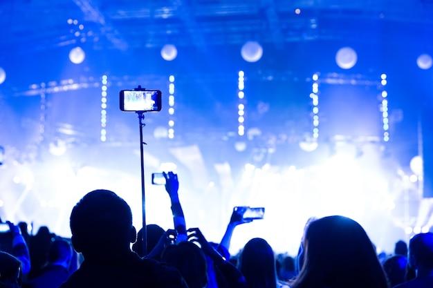 스마트폰을 손에 들고 콘서트에 참석한 관중들의 실루엣. 장면은 스포트라이트로 아름답게 비춰집니다.