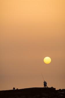 백그라운드에서 태양 어부의 실루엣