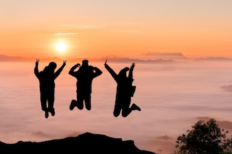 Silhouettes of friends jumping on mountain peak. Sport and active life concept