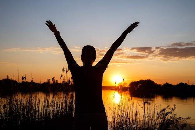호수에서 일몰에 소녀들의 실루엣, 나무 뒤에 태양이 지고 물에 아름다운 반사