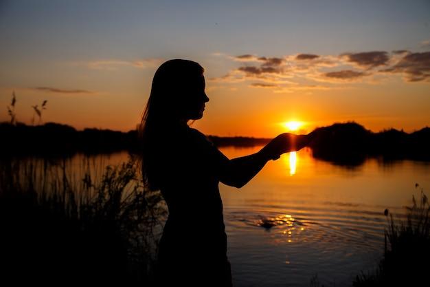 湖に沈む夕日、木の後ろに沈む太陽、水の美しい反射の女の子のシルエット