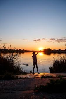 湖に沈む夕日、木の後ろに沈む太陽、水の美しい反射の女の子のシルエット Premium写真
