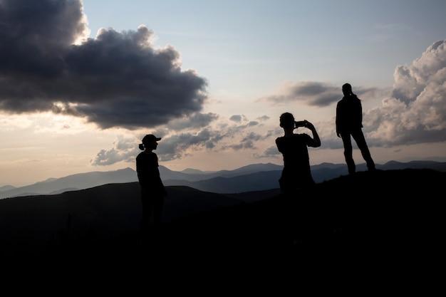 일몰, 아름다운 황혼의 하늘에 산에서 촬영 된 여자 관광객의 실루엣