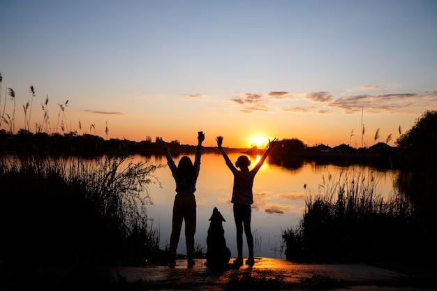 Силуэты девушек с собакой на закате на озере, солнце садится за деревья и красивые отражения в воде