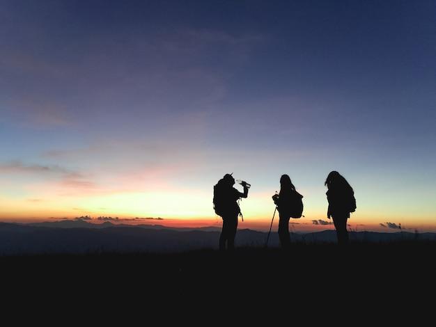 グループハイカーのシルエット山頂からの日没の景色を楽しむリュックサックを持つ人々。旅行のコンセプト、ビンテージのフィルタリングされた画像