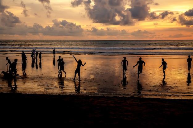 海のビーチで日没時にサッカーをする男のシルエット。