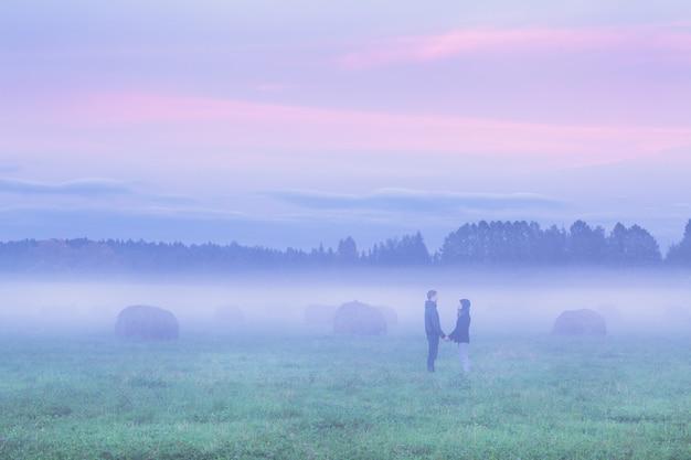 互いに向かい合って立って、日没時に干し草の山と霧のフィールドで手をつないでいる男性と女性のシルエット