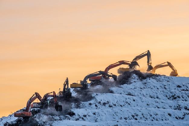 겨울에 주황색 일출이나 일몰 하늘을 배경으로 쓰레기 더미에 있는 거대한 산에서 일하는 많은 굴착기의 실루엣입니다. 인간 폐기물의 처리. 심각한 자연 오염.