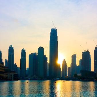 Силуэты новых небоскребов и их отражение в воде на закате, дубай-сити, оаэ
