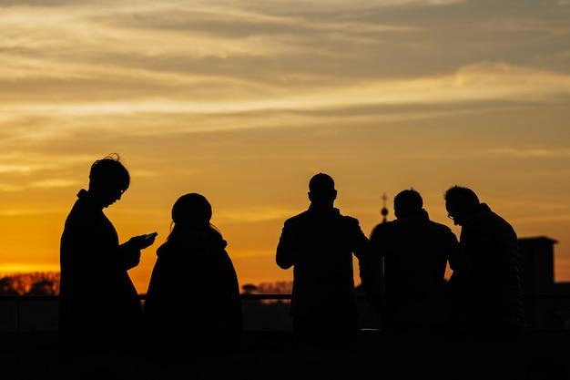 Силуэты людей, наслаждающихся закатом во флоренции, италия. вид сзади.