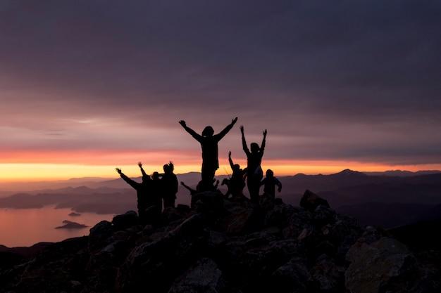 Силуэты людей на вершине горы