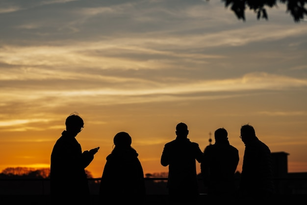 イタリア、フィレンツェの夕日に携帯電話と自撮り棒で夕日の写真を撮る人々のシルエット。