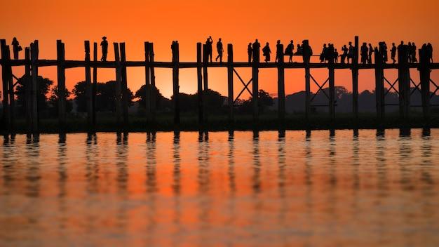 ミャンマー、マンダレーのu beinbridgeで日没時に歩く人々のシルエット