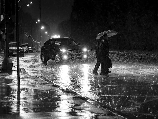 Силуэты людей с зонтиком, идущих по пешеходному переходу ночью во время ливня