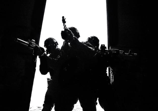 Силуэты тактической группы сил специальных операций полиции, бойцы спецназа, прицеливающиеся из штурмовых винтовок, стоя плечом к плечу в ярко-белом дверном проеме. штурмовая военно-тактическая группа