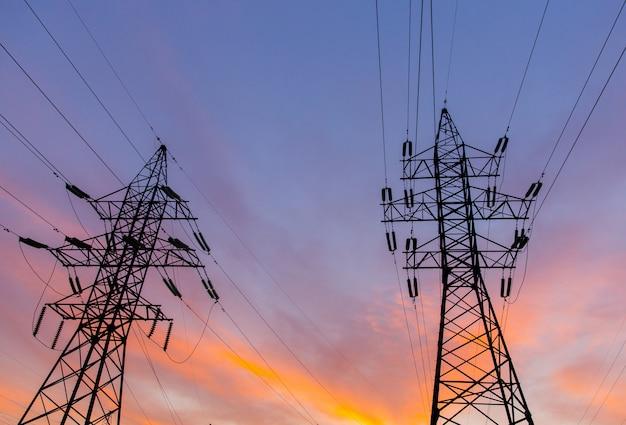 Силуэты линий электропередач на закате. ярко-оранжевый городской закат