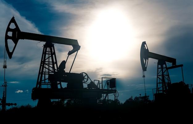 Силуэты насосных станков с поршневым насосом на нефтяной скважине на фоне тревожного неба