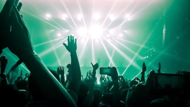 Силуэты поднятых рук на музыкальном концерте или фестивале