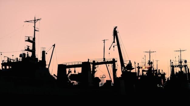 Силуэты кораблей и контейнерных кранов в морском порту, фоне заката. декорации индустриального пейзажа.