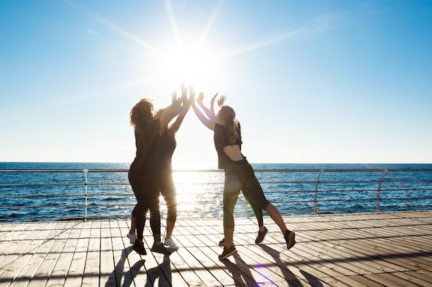 日の出で海の近くにhighfiveを与える陽気な女性のシルエット