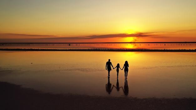 Силуэты трех, папы, мамы и маленькой дочери, гуляющие по мелководью озера