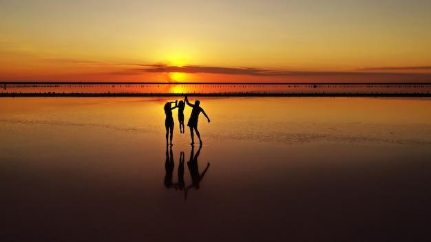 Силуэты трех, папы, мамы и маленькой дочери, гуляющие по отмели озера