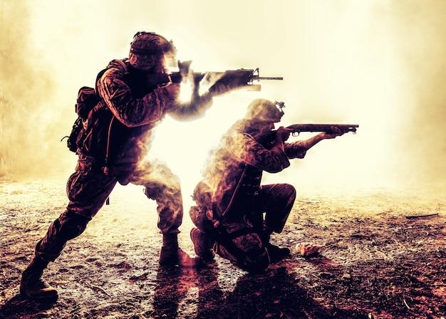 두 명의 육군 병사, 행동하는 미 해병대 팀, 포위 된 화재 및 연기, 돌격 소총과 기관총으로 사격, 공격 임무 중 진압 총으로 적을 공격하는 실루엣