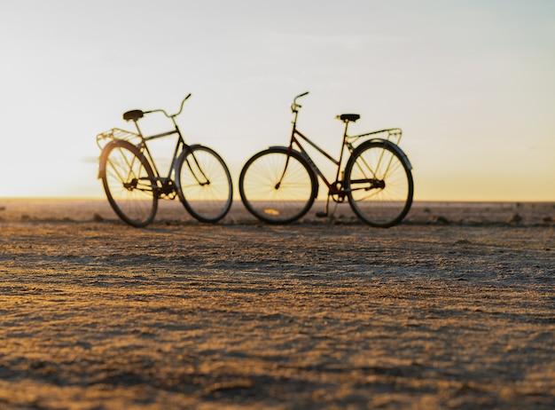夏の日の夕日のロマンスに対する2台の自転車のシルエット