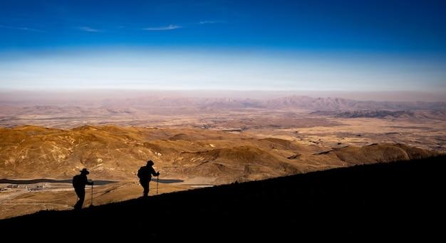 日の出の時間の人々が登っているトルコの火山エルジェス山でのハイキング中の2人のシルエット...