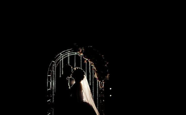 夜の結婚式の祭壇の前にキスする結婚式のカップルのシルエット