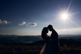 山の風景の前に太陽の光の中に立っている結婚式のカップルのシルエット