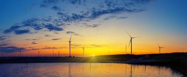 Силуэты электростанции ветрогенераторов на озере на закате