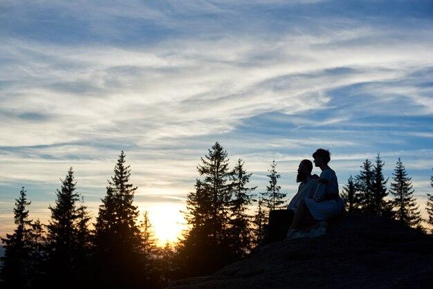 저녁에 산 꼭대기에 앉아 젊은 부부의 실루엣