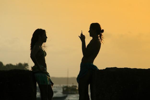 日没時の若者のシルエットとスマートフォンで写真を撮ります。