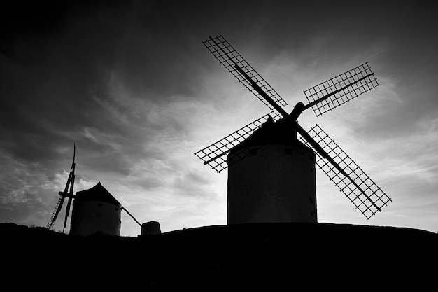 Silhouettes of old windmills on a cloudy day