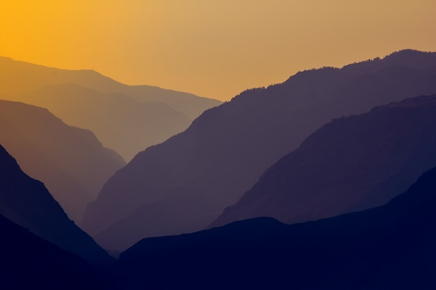 Silhouettes and outlines of a mountain massif in the setting sun