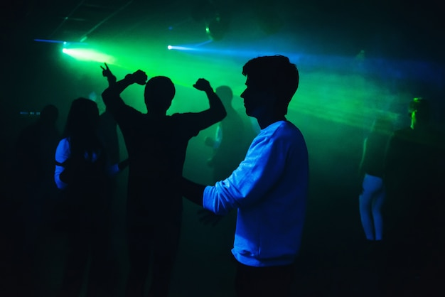 Silhouettes of people dancing in nightclub on dance floor at party